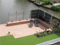 Wat een prachtige tuin met mooie antracieten luxe schuttingen gecombineerd met een naturelbruine vlonder